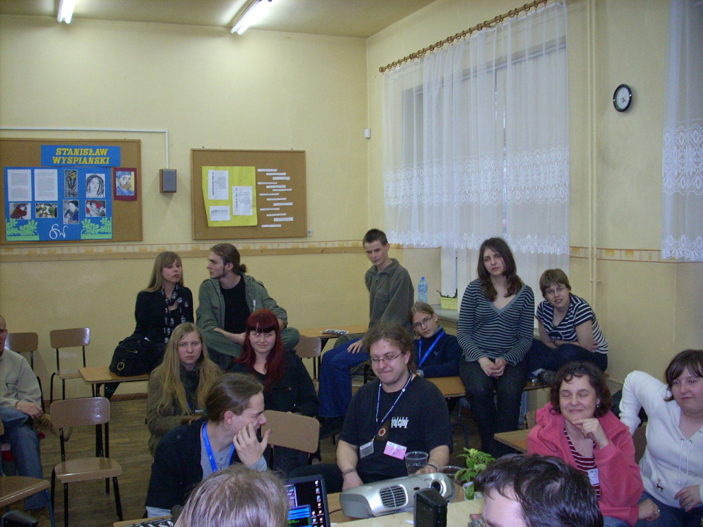 Multiple people in a clasroom sitting on both chairs and tables.