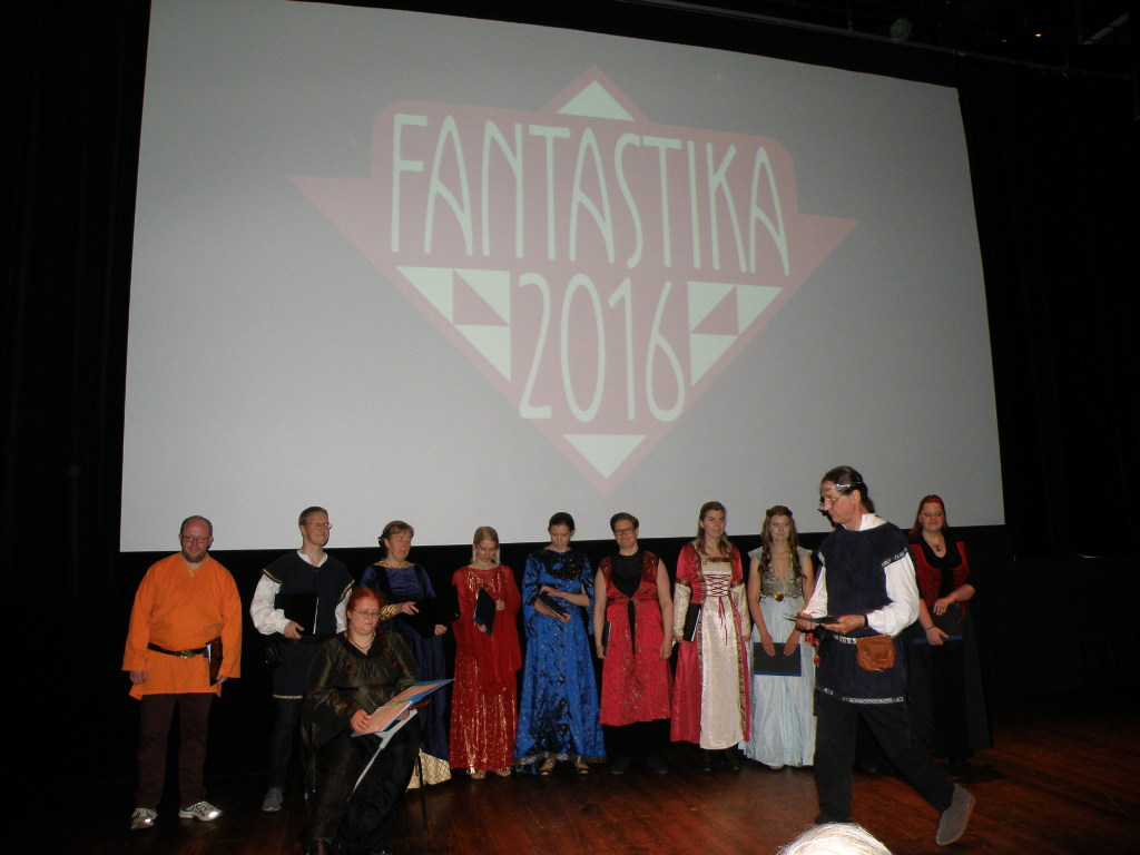 People in historic/fantasy costumes on the scene. The screen behind them shows Fantastika 2016 logo.