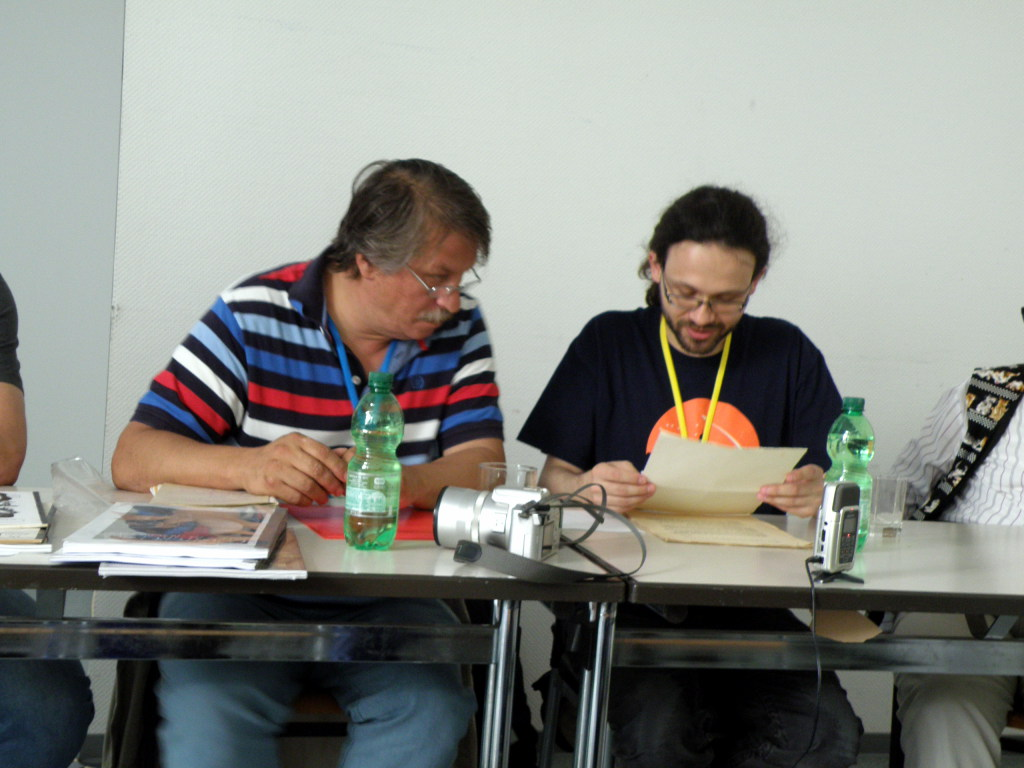 Two men sitting behind the table. One looks at the sheet of paper he is holding. The other one is also looking there.