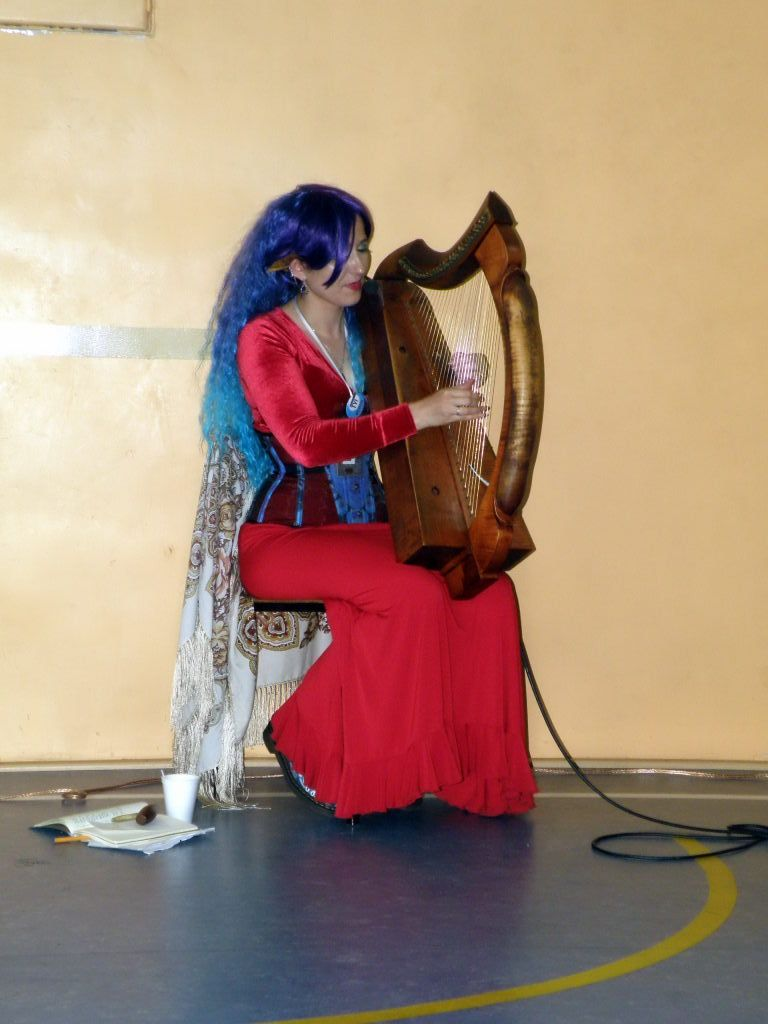 Woman with blue hair sittinf and playing celtic harph..
