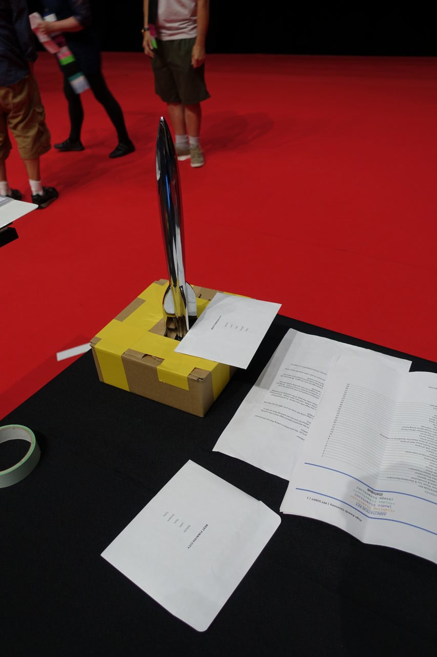 Hugo Award standing on the table with some papers. The base is closed in a box and only the rocket itself is visible.