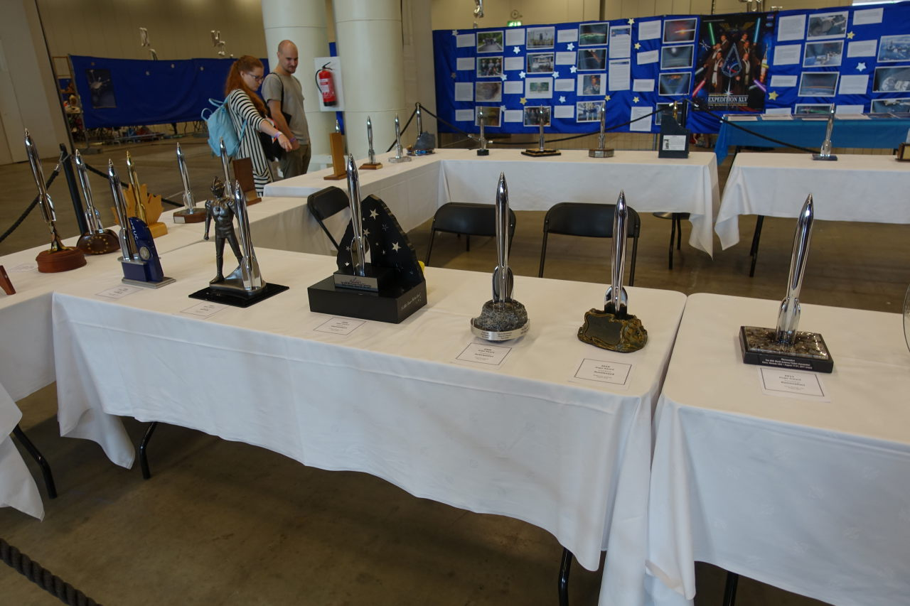 Exhibition showing multiple Hugo Awards on tables covered with white clothes.