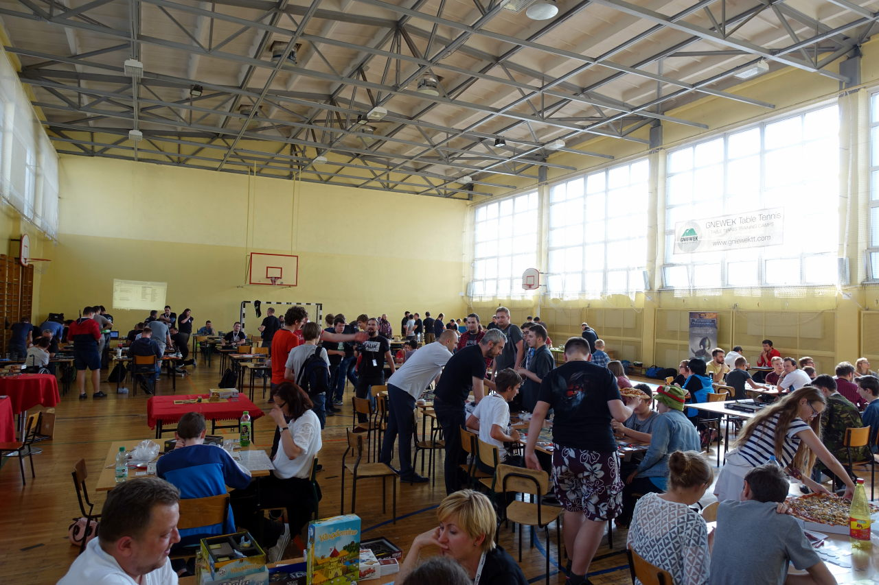 Gymnasium filled with people. People sit around tables and play games.
