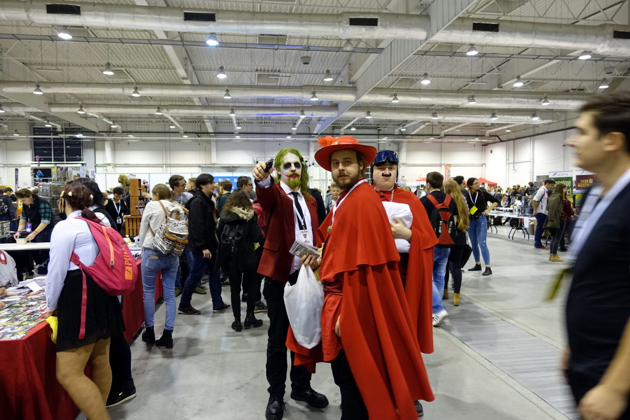 Three cosplayers in one of the halls. Two are in red robes and one is dressed as Joker.