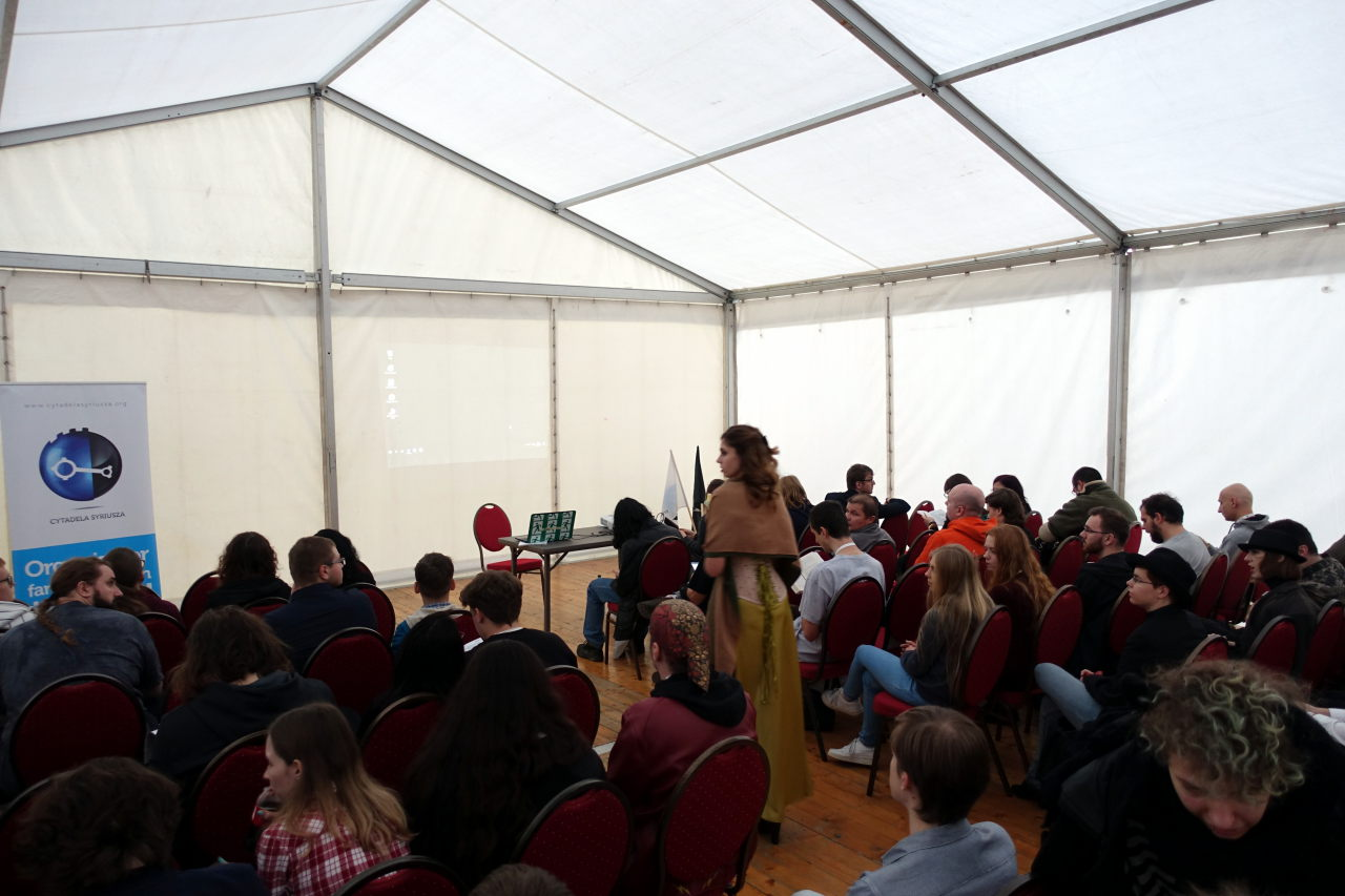 Interior of the programme tent. Two regions are filled with people sitting. In the middle woman in a dress is walking