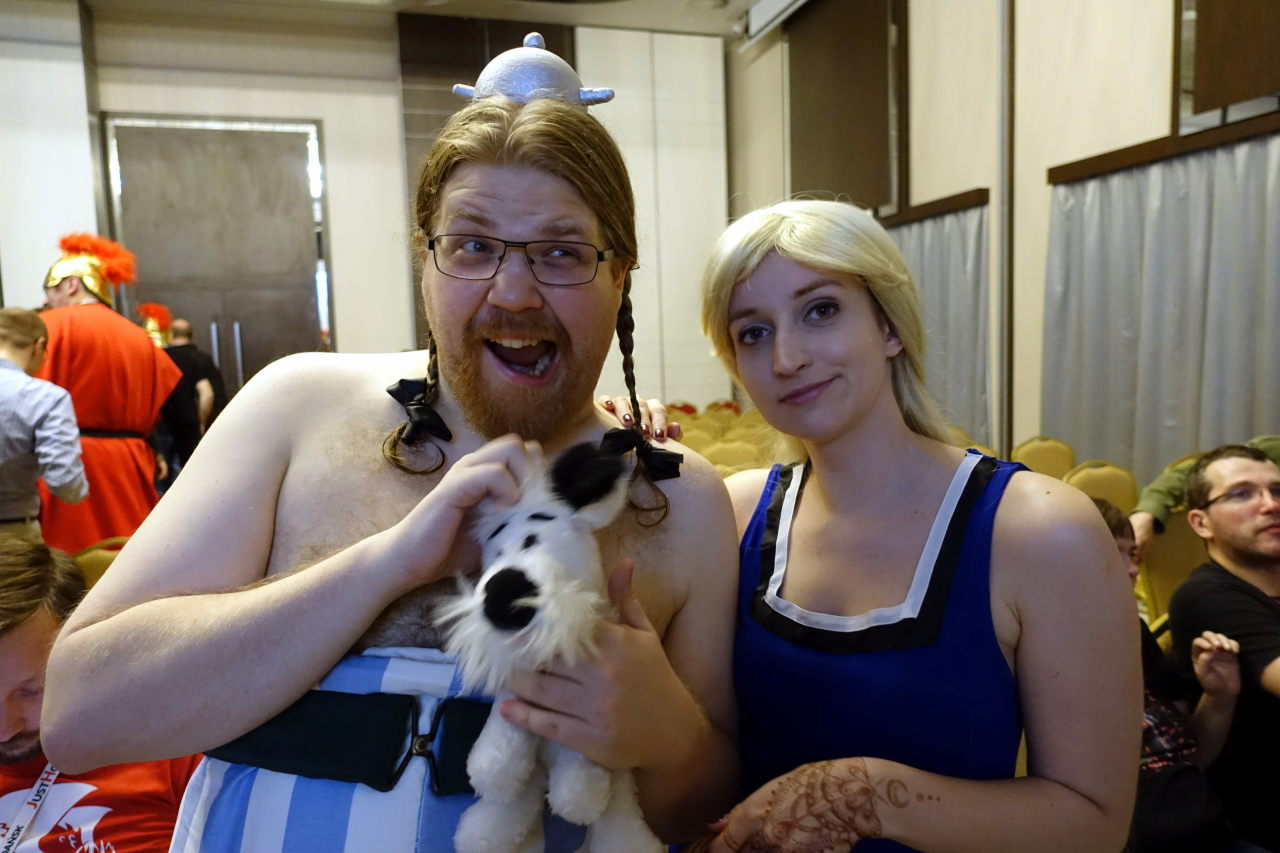 Picture shows fan dressed as Obelix with small dog plush toy and second fan dressed as Falbala.