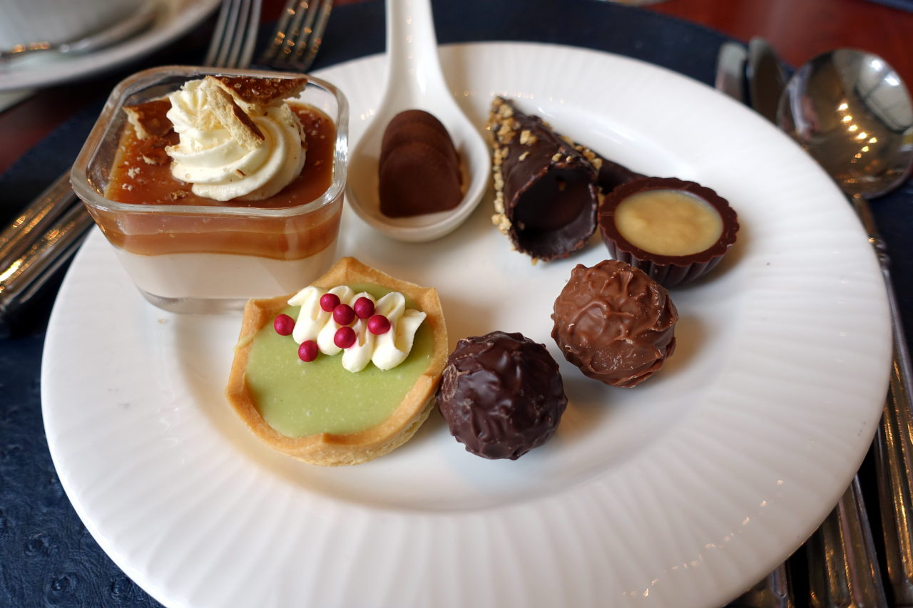 Picture shows white plate with two chocolate truffels, chocolate cup, chocolate cone, spoon with some chocolate on it, chocolate mousse and a cake.