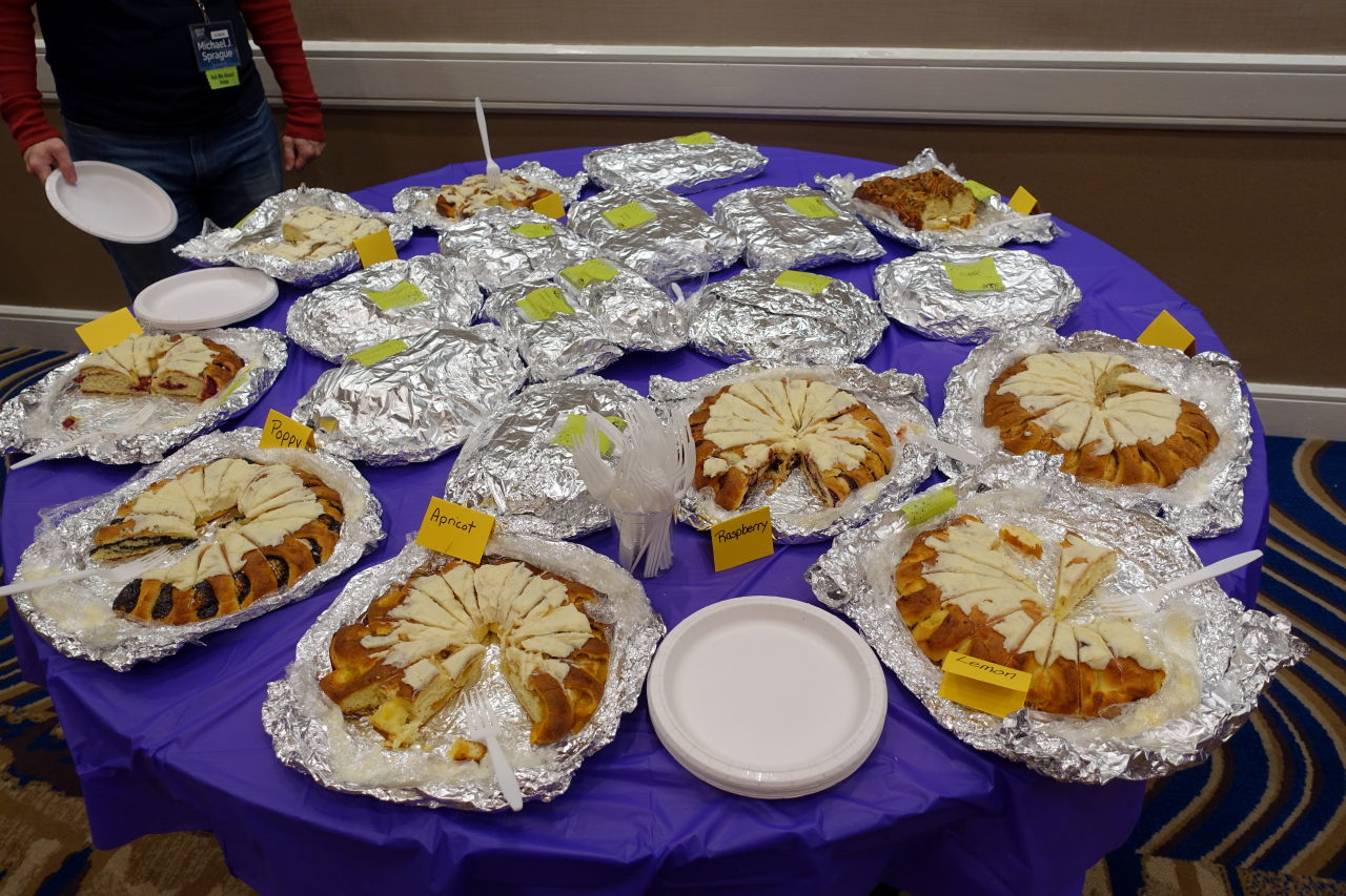 Picture shows multiple cakes on a table covered with violet tablecloth.