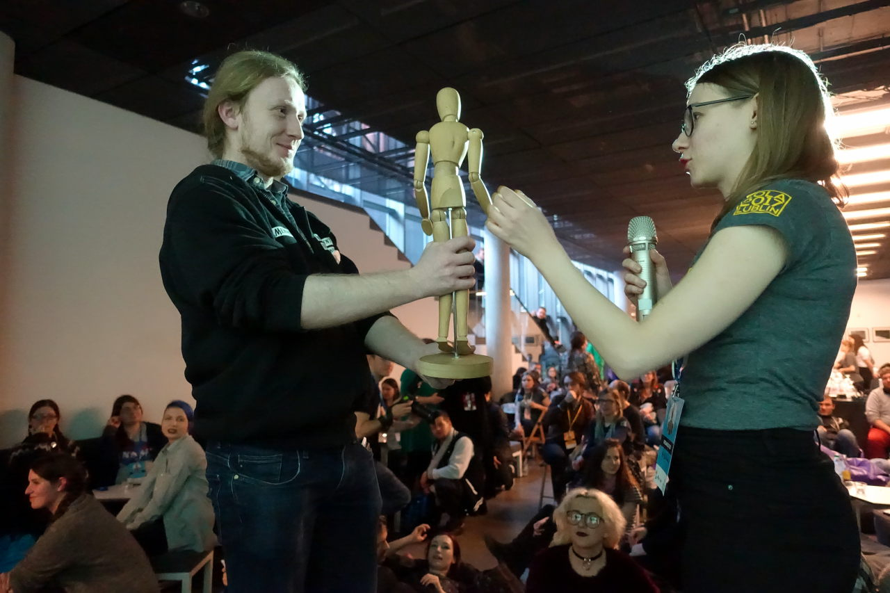 Picture shows woman giving to the mean a wooden figure. Behind them there is a room packed with people.