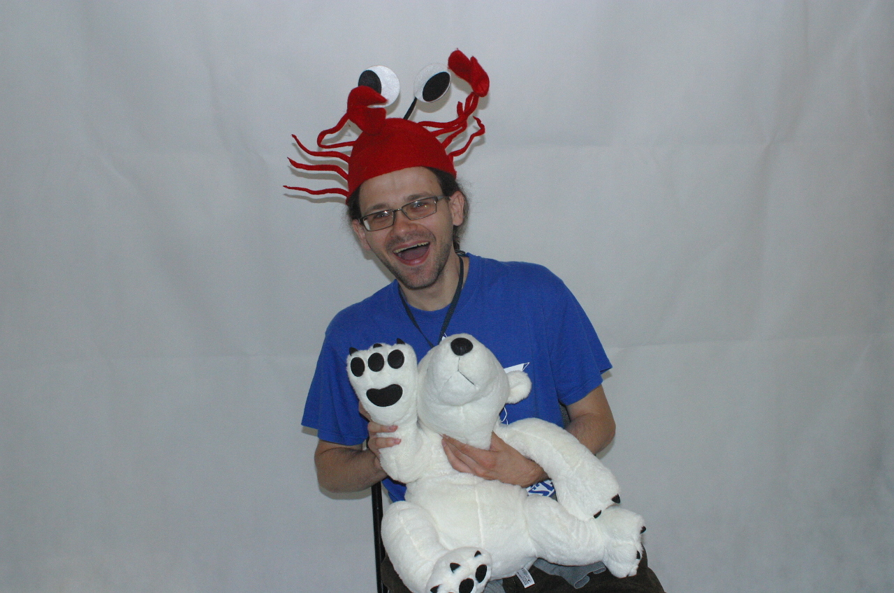 Man sitting and laughing. He wears crayfish hat and he keeps polar bear on his knees.