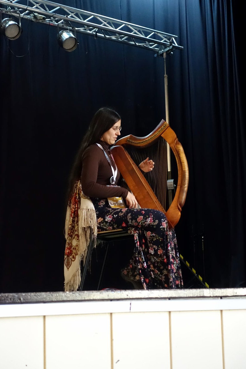 Woman playing a Celtic harp on a stage.