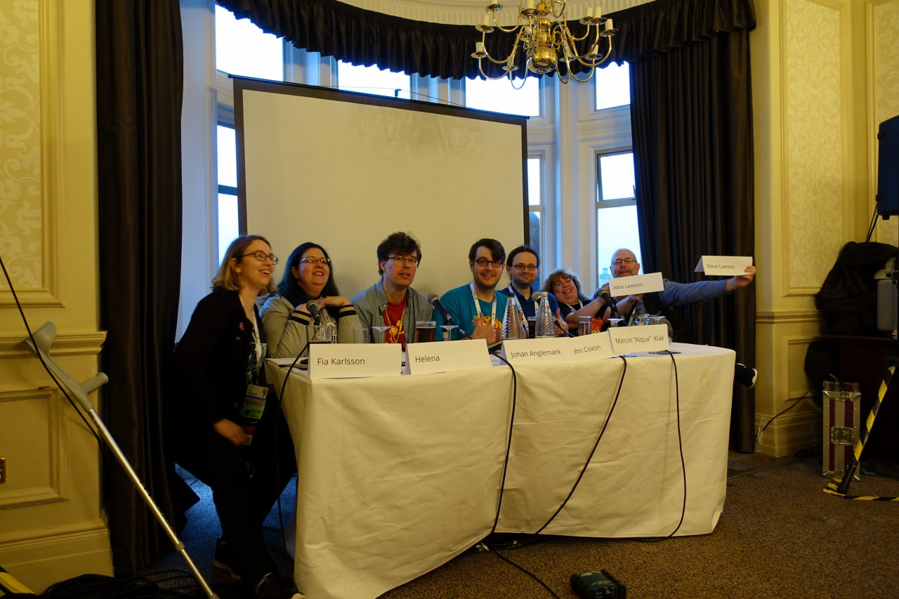 Seven people sitting behind the table. Two are holding their name tags in their hands.