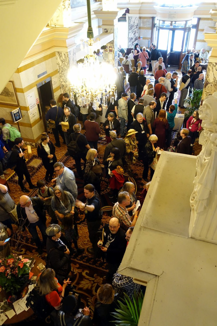 Picture was taken from above. It shows a crowd of people in an old hall of the hotel.