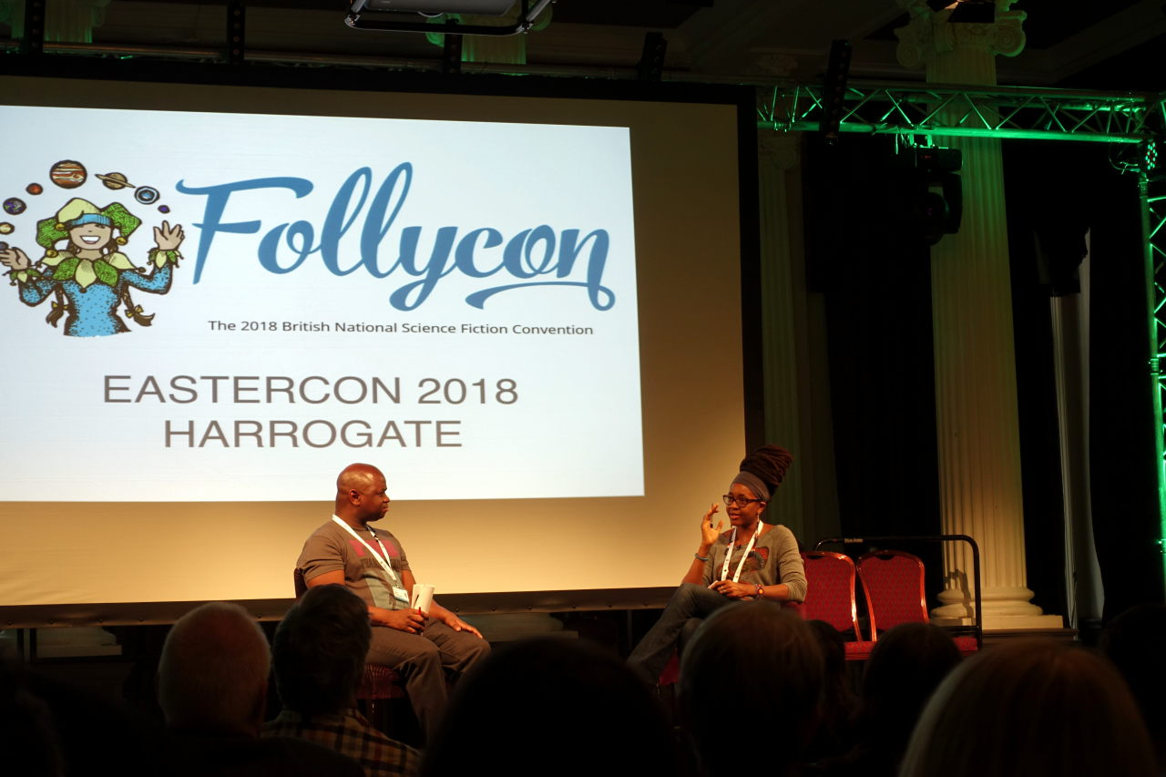 Men and women are sitting on the chairs. Screen behind them shows Follycon Logo. Below the logo it is written Eastercon 2018 Harrogate.