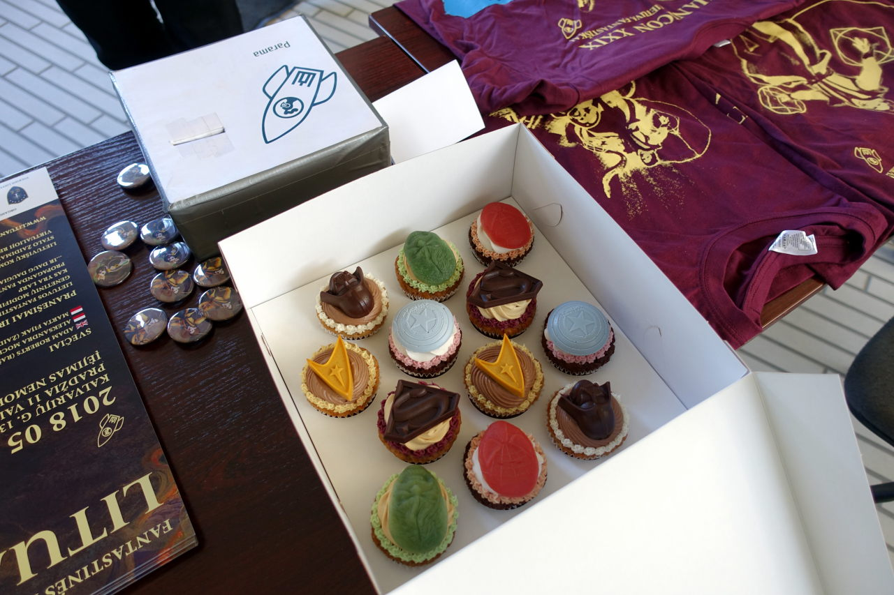 Picture shows some stuff on the table. In the center there is a box with cupcakes decorated with geeky symbols.