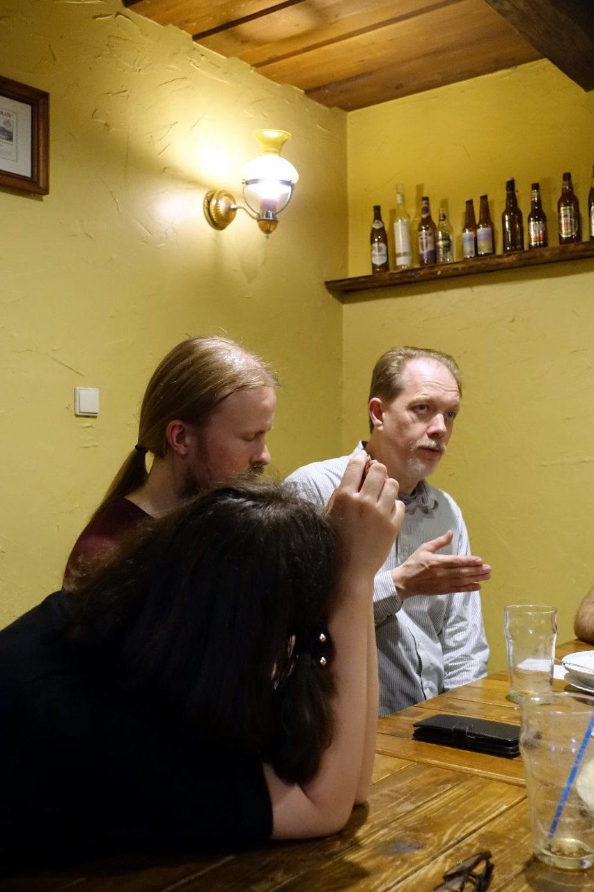 Picture shows a scene in a pub. There are three people sitting at the table. One of them is speaking and the other two are listening. One of the listeners is leaning over table and we can see just the back of her head.