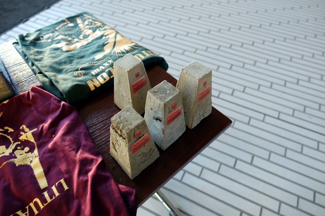 Picture shows four miniature concrete monuments. Two t-shirts are also visible