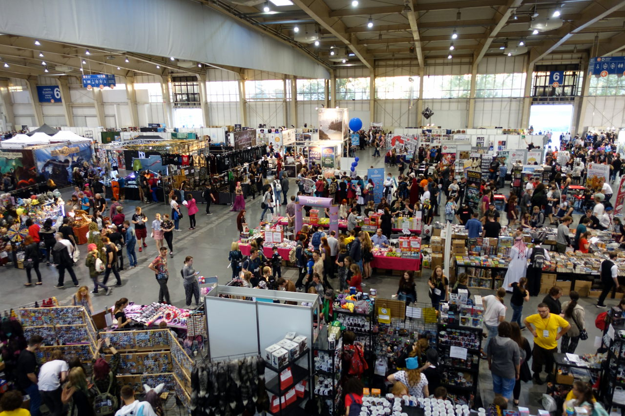 Picture was taken from above. It shows part of a big hall filled with merchant stalls and people walking between them.