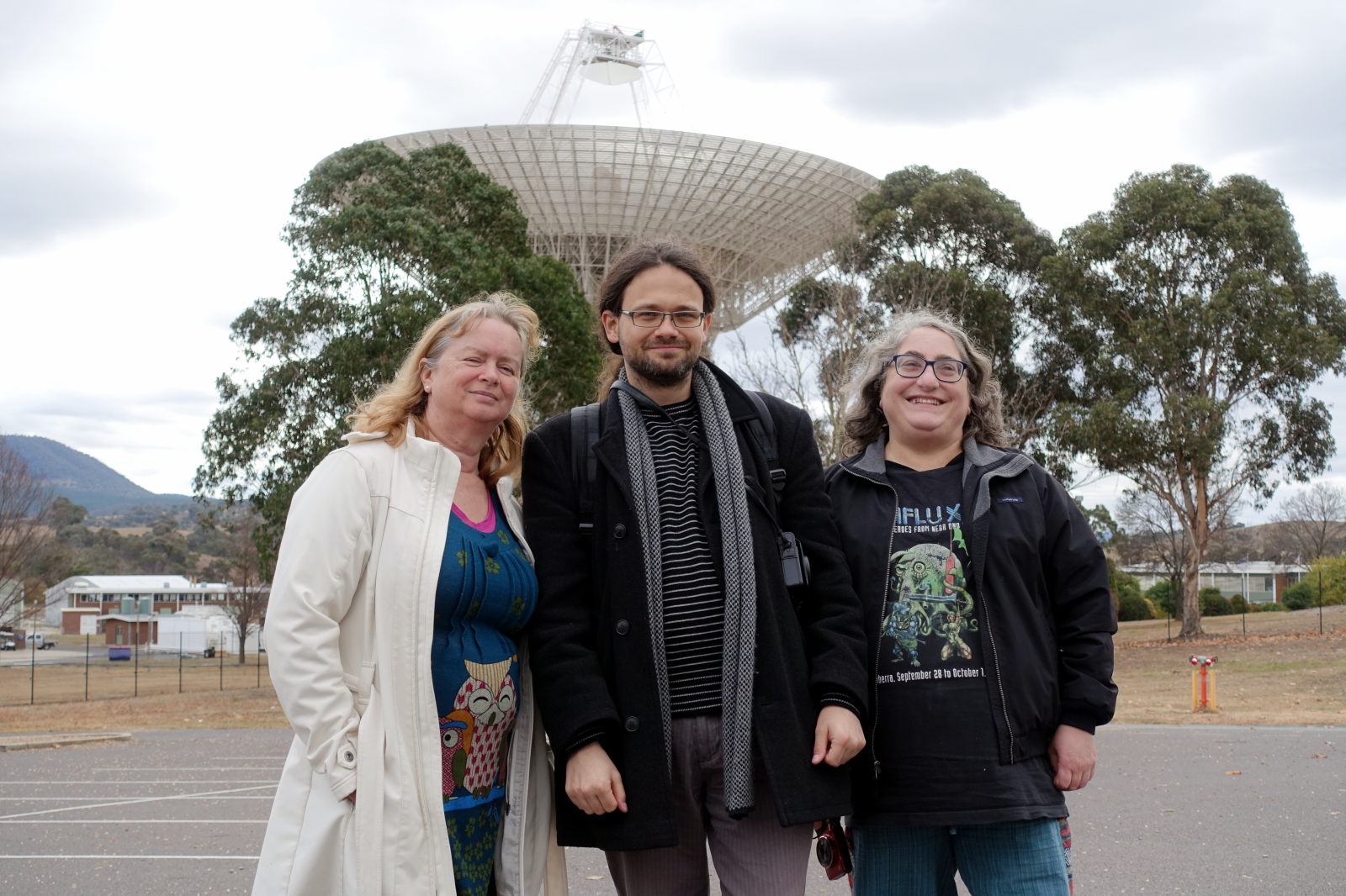 Three people posing for picture in front of big antenna dish.