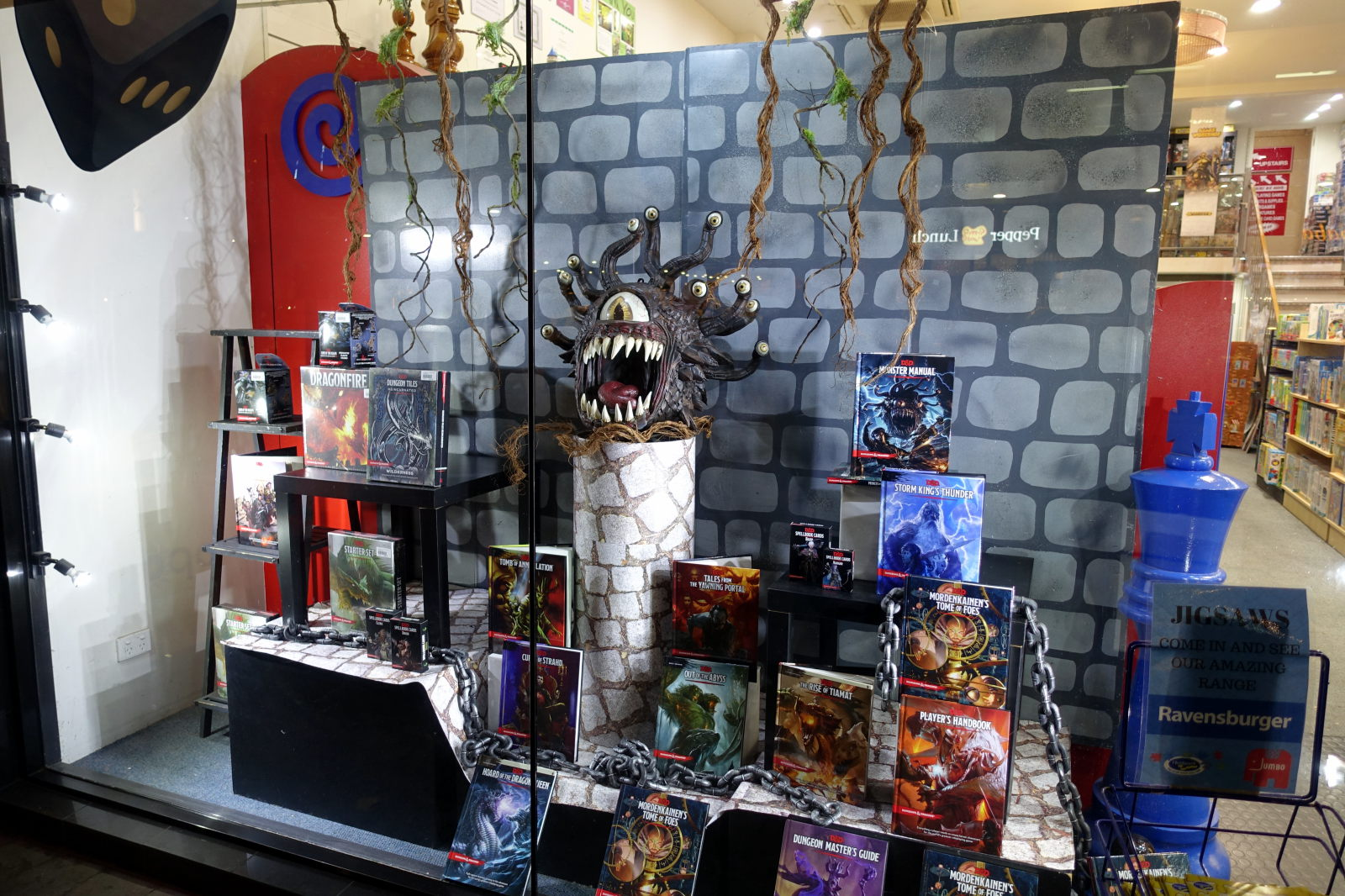 Display window with few RPG rulebooks and a figure of beholder.