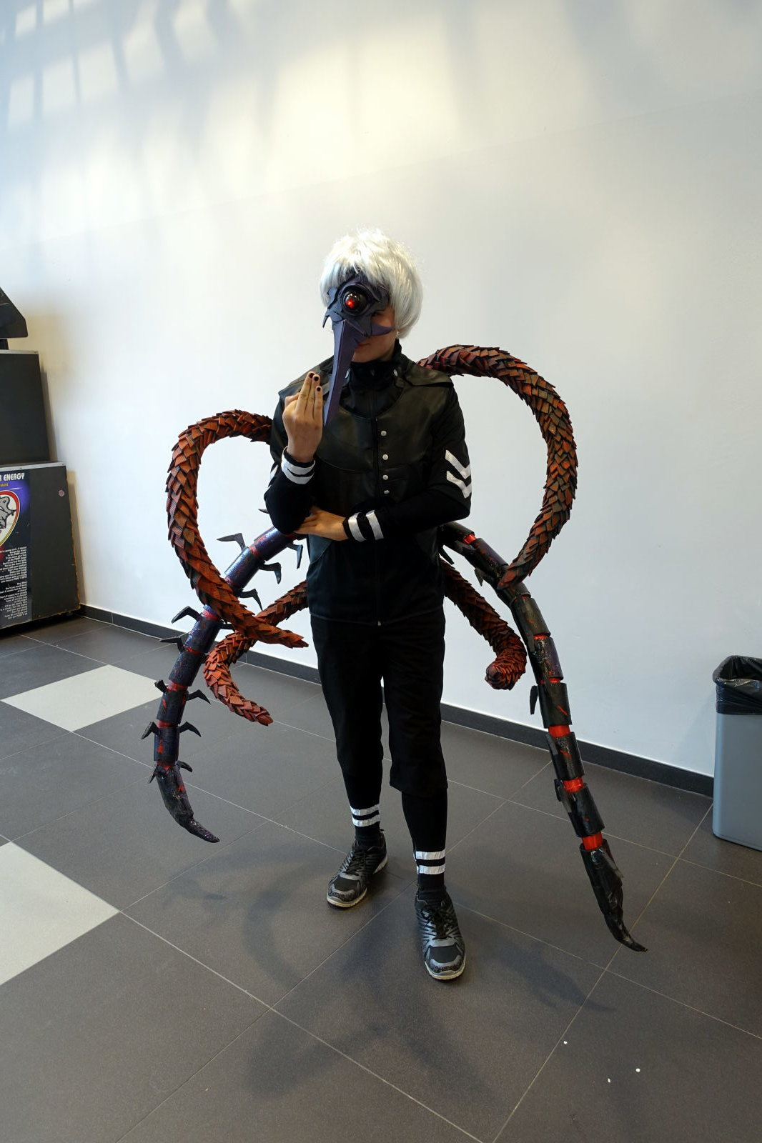 Masked person in costume. Apart from the mask the most notable feature of the costume are three pairs of arthropod like legs.