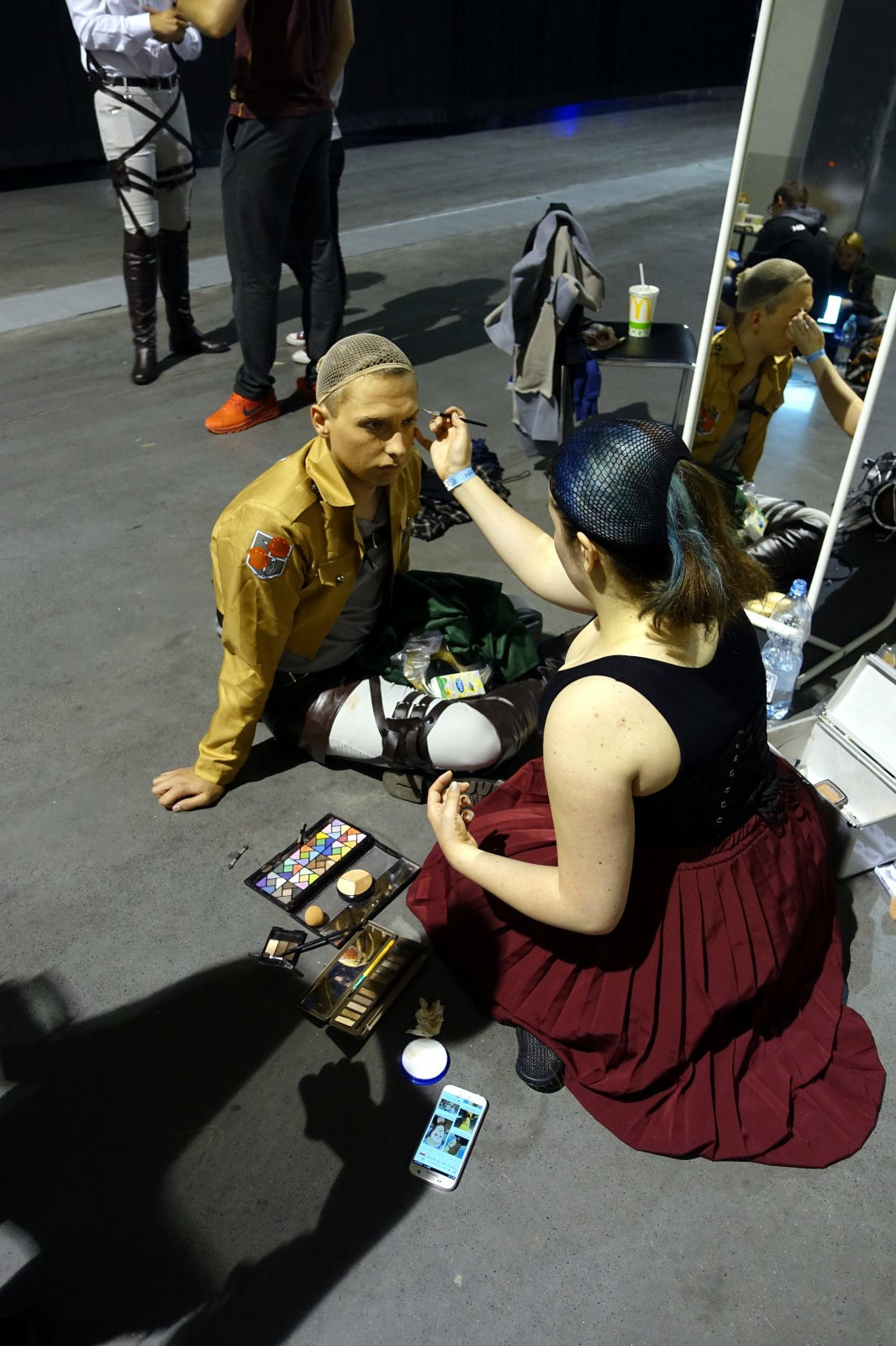 Two people sitting on the floor. One is helping the other with make up.