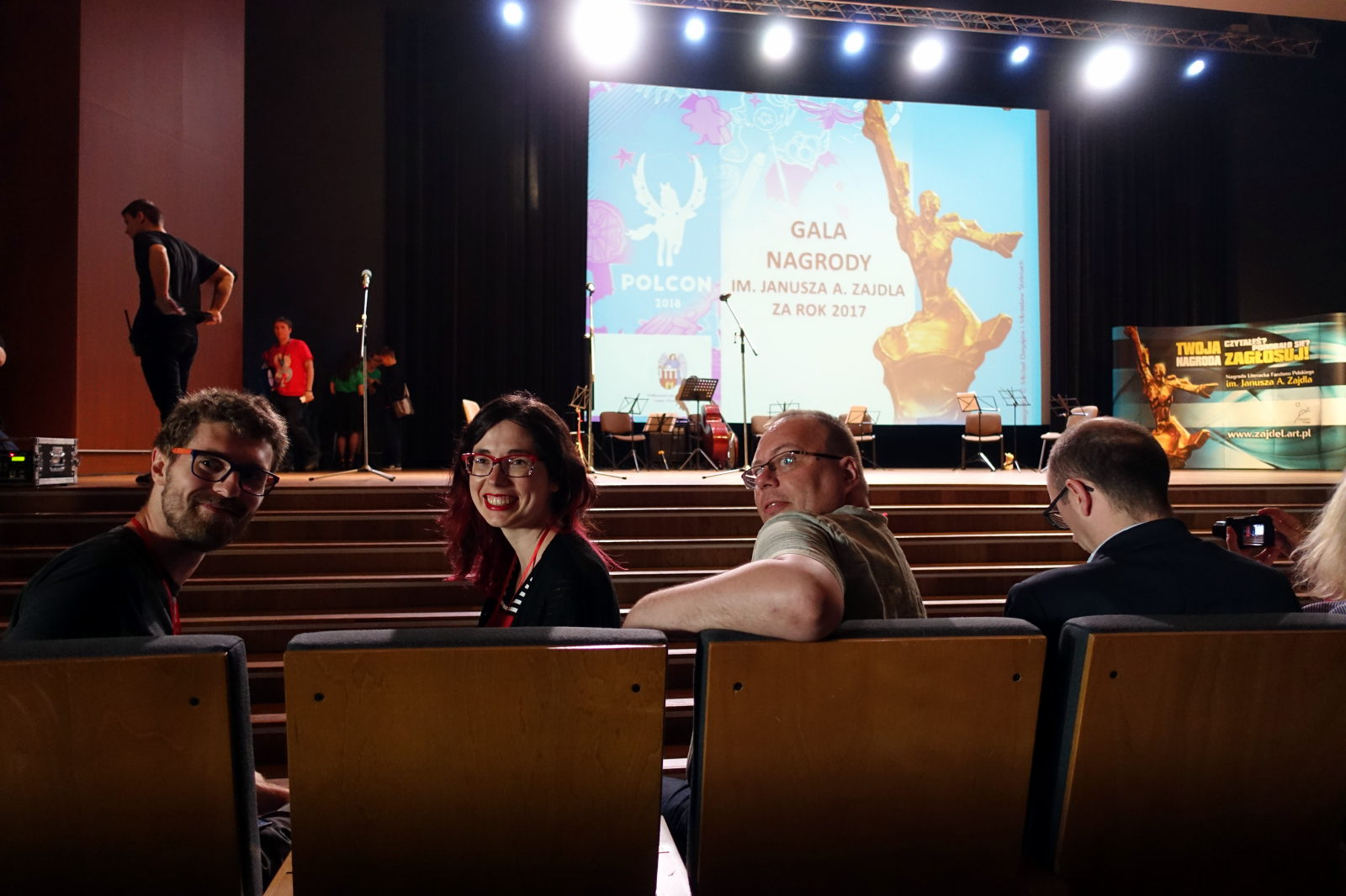 Three people sit in the fron row of an auditorium are turned back to face the photographer. In fron of the first row there is a scene with big screen showing convention logo and Janusz. A Zajdel Award statuette.