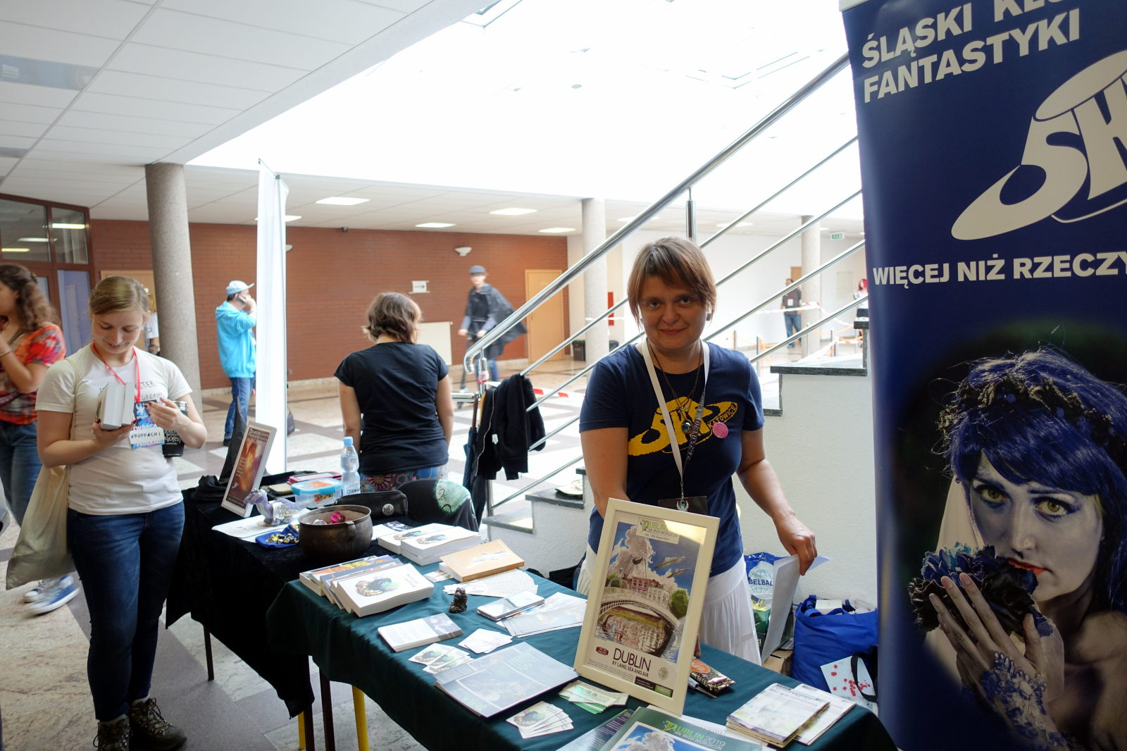 Woman standing behind the table and smiling. There are books, posters and flyers visible on tha table. To the right there is a roll-up promoting ŚKF. There are a few other peopel visible.