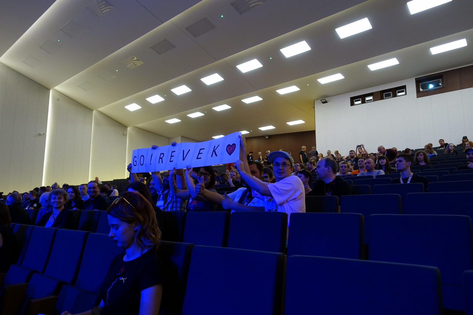 Audience in a big auditorium. Few people hold banner with inscription 'GO! REVEK'.
