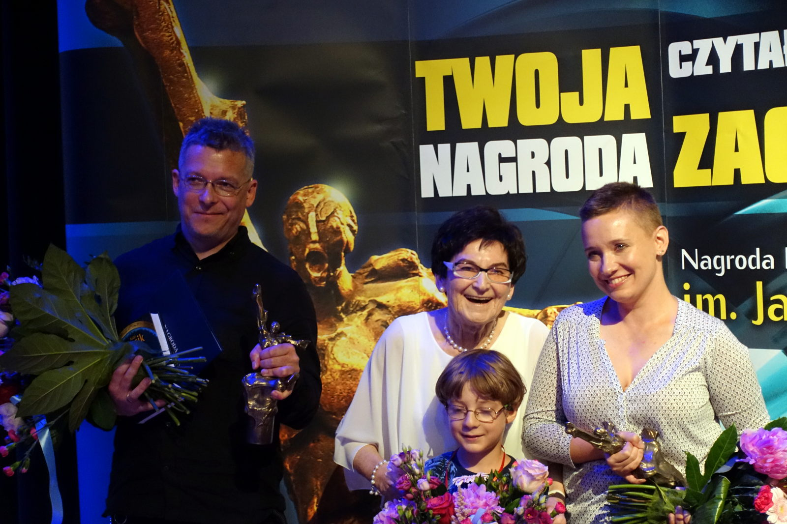Three adults and a child posing in front of the big Janusz A. Zajdel Award poster.