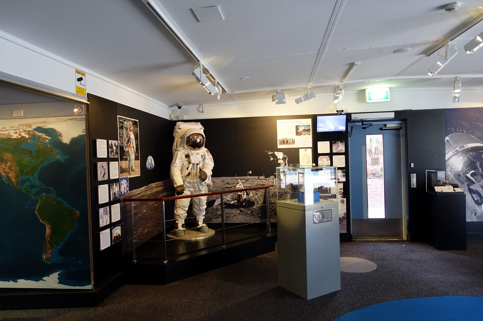 Picture shows one of the museum rooms. The most disctinctive part is a model of the astronout in front of the big wallpaper showing moon's surface.