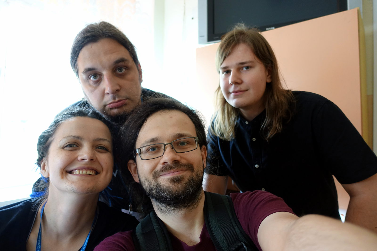 Four people posing for a selfie. One of them pretends to be sad.