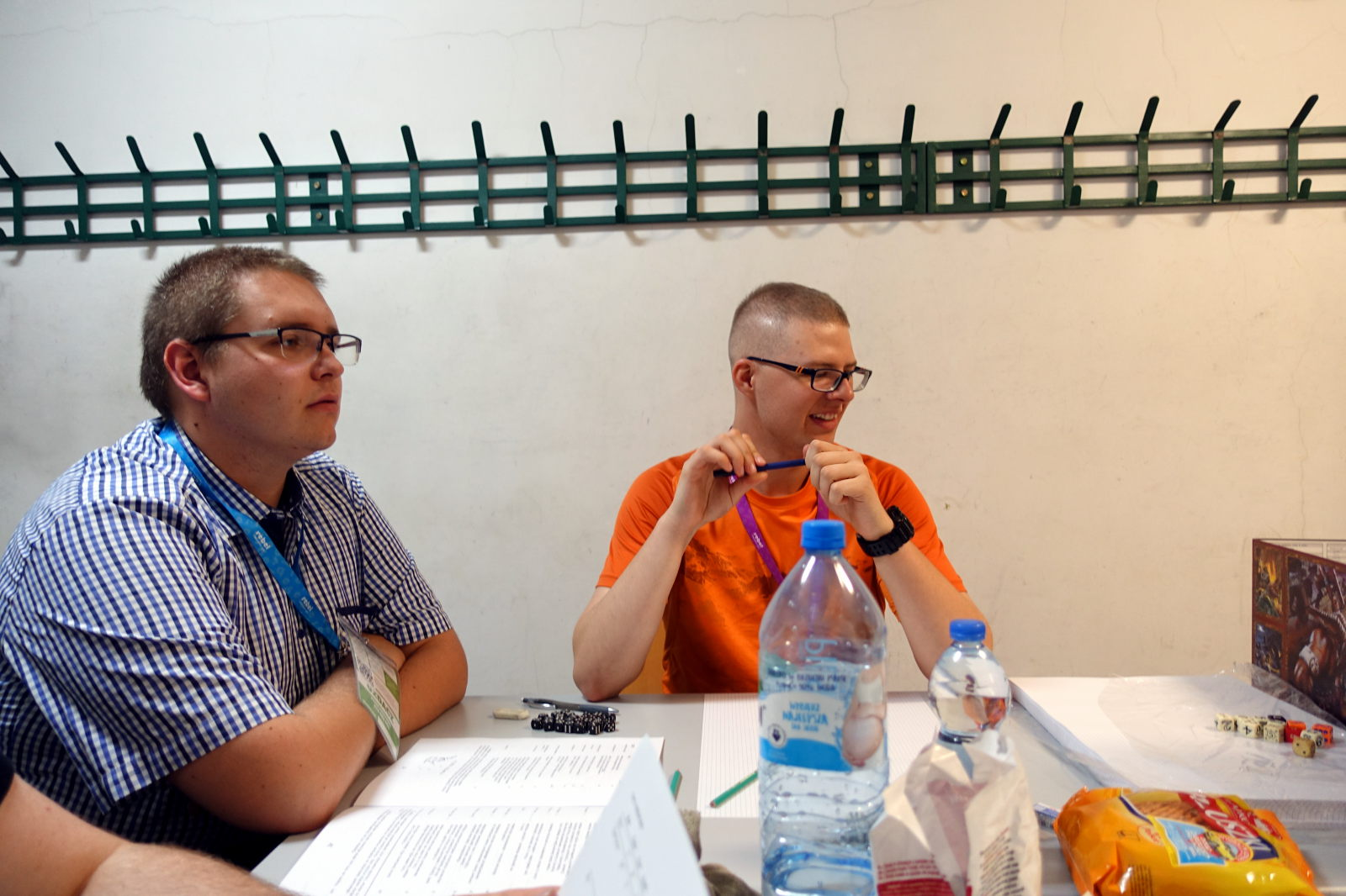 Two man sitting at the table. One to the left wears shirt. Second wears orange t-shirt.