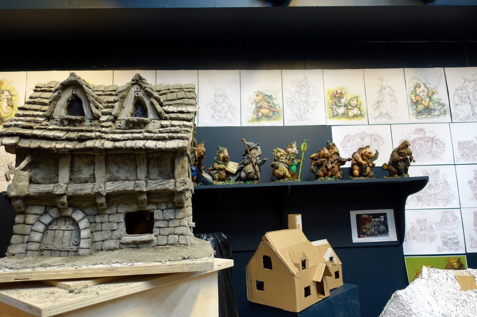 A sculpture of a house and a house model made from carton. Behind them there is a shelf with models of small animals. Some pictures are visible on the wall.