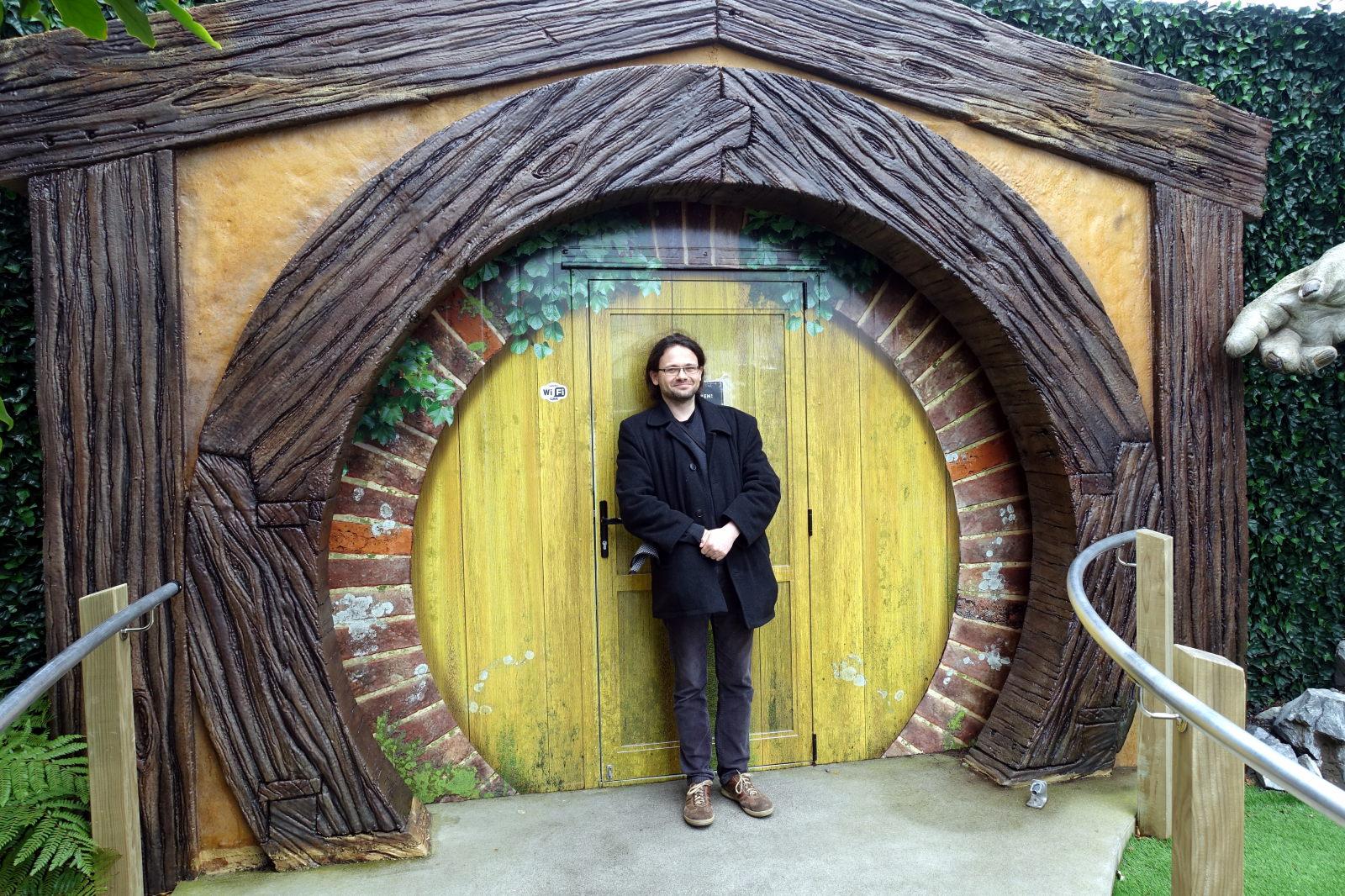 Man standing in front of the door to a hobbit hole.