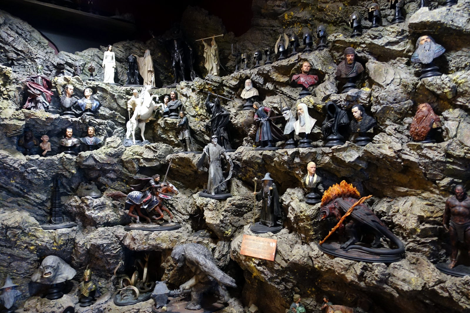 Figures from The Lord of the Rings and The Hobbit  presented on a rock like shelves.