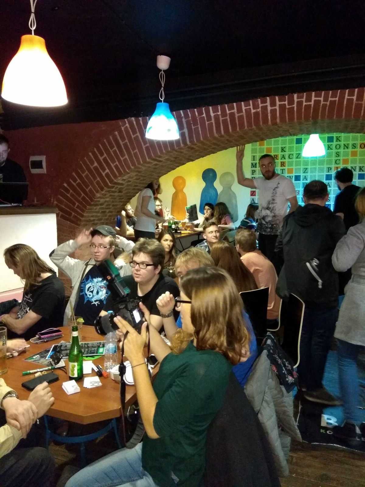 Multiple people sitting and standing in a bar.