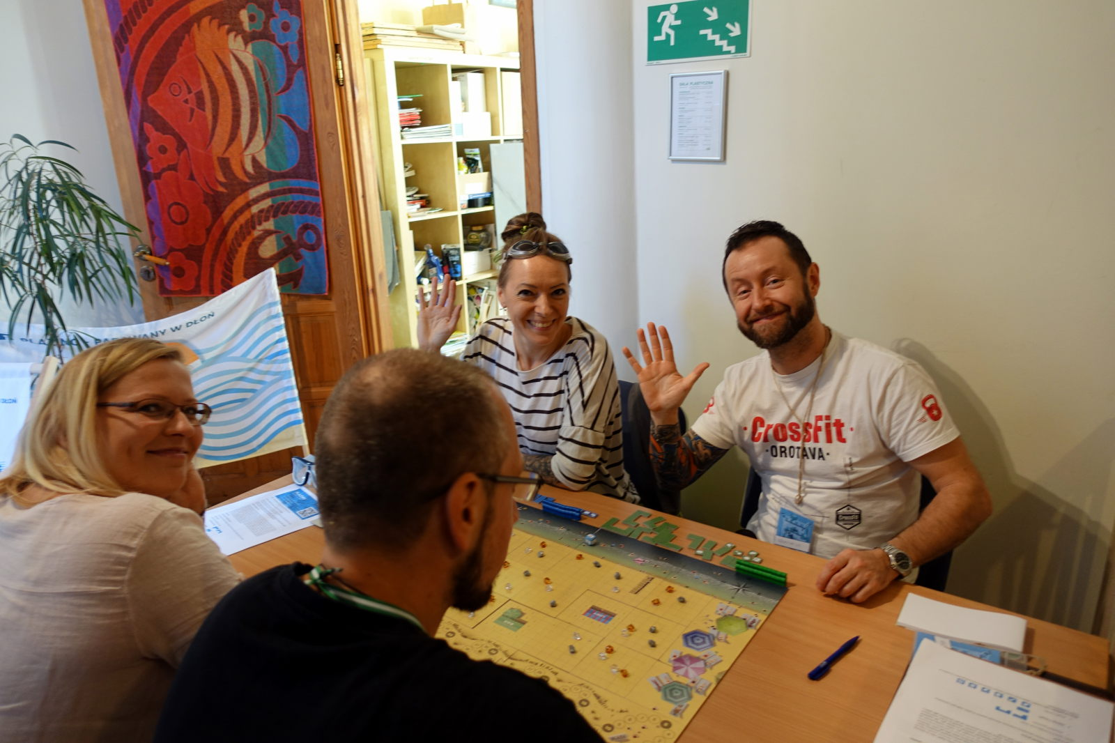 Four people playing the game. Two of them wave their hands to the photographer.