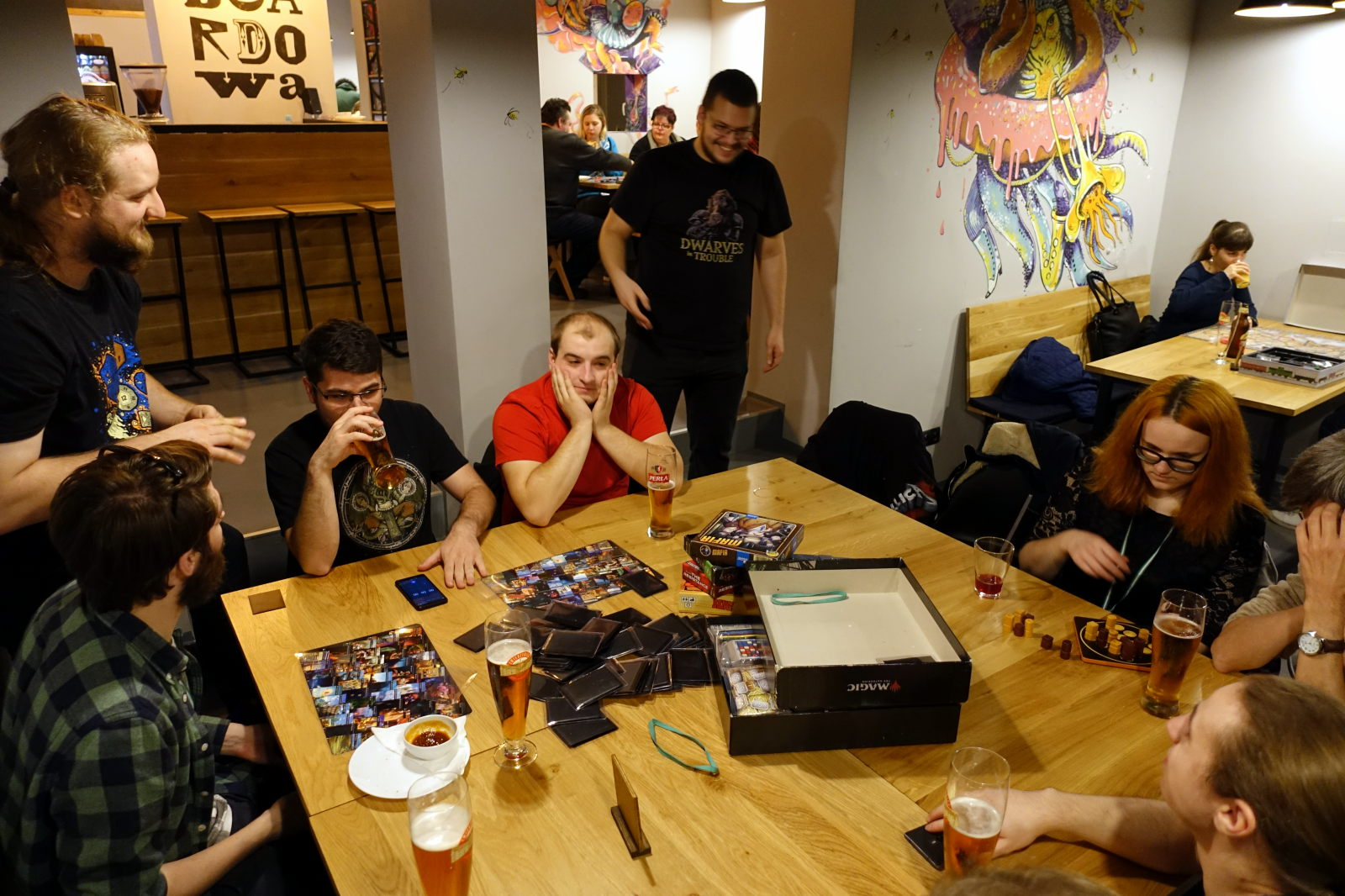 Eight people sitting and standing around a table. There are some board games on the table and a few people have their beer.