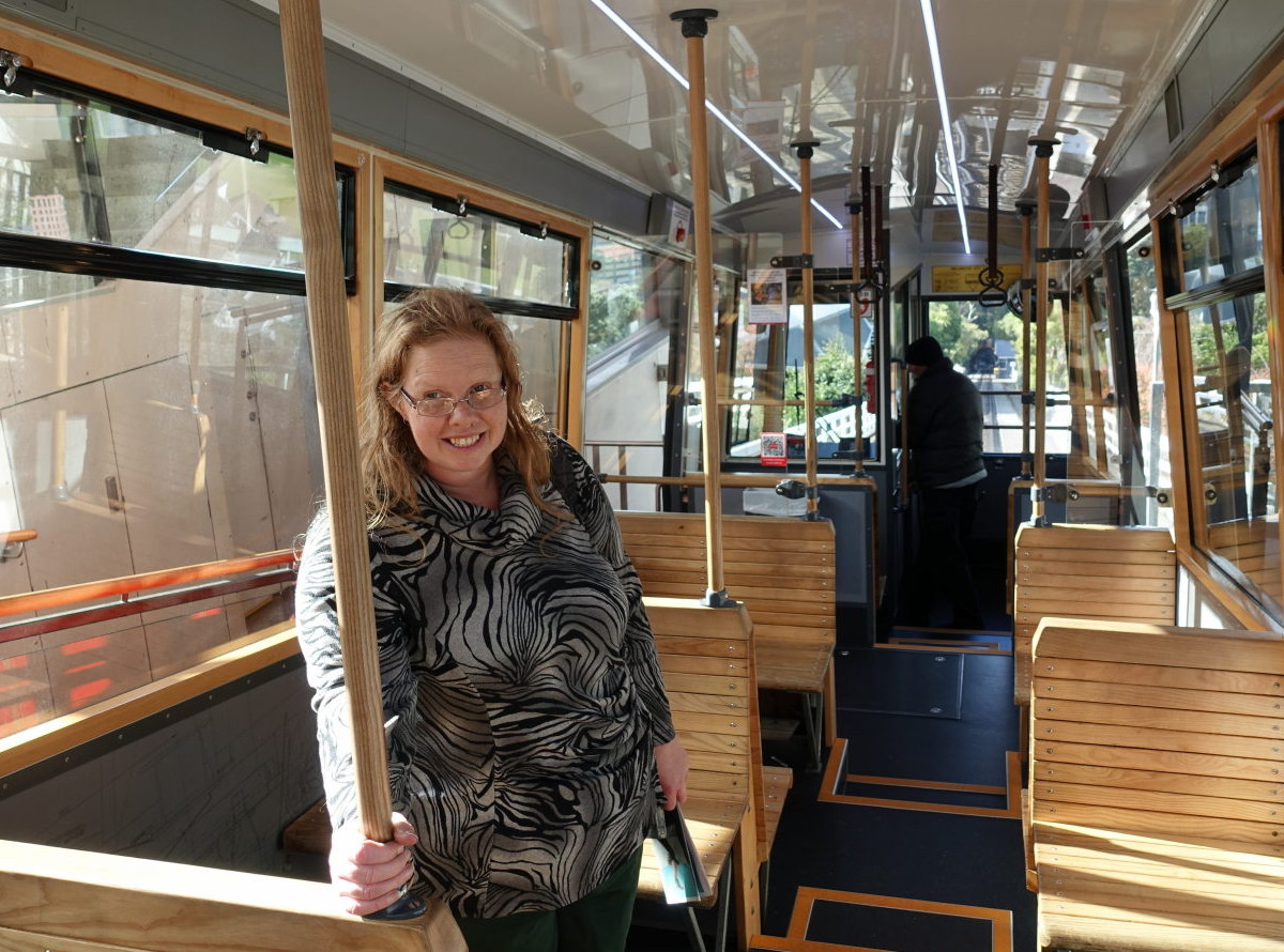 Woman stands in a tramcar and smiles.
