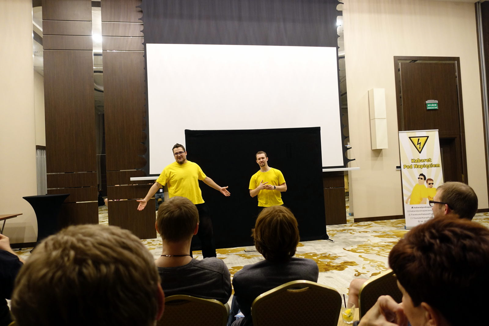 Two men in yellow shirts stand in front of some audience. Only a few heads of the audience members is visible.