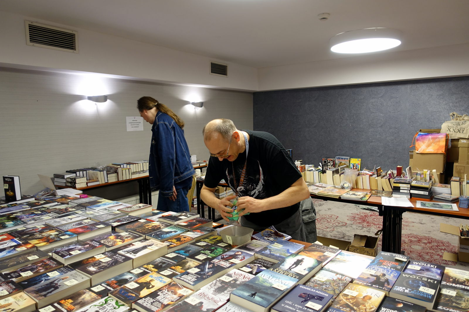 Big flat surface is covered with books. Behind it there is a man tearing the foil bag. In the background there is another man standing and there are two tables with books on them.