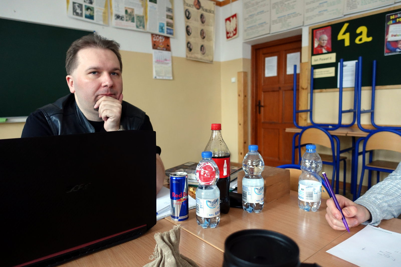 Man sitting behind a table. In front of him there is a laptop and a few bottels and a can.