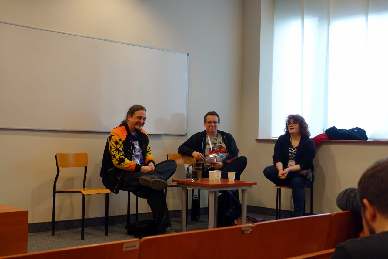 Three people sitting forming a panel. One of them is visibly laughing.
