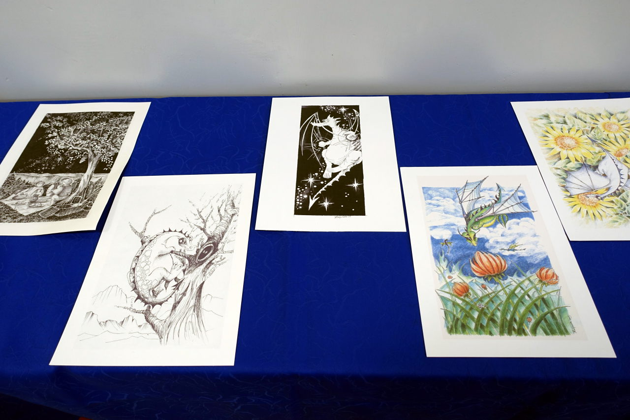 Five pictures on a blue canvas. Four of them depicts dragons. Three pictures are black and white and two are colour.