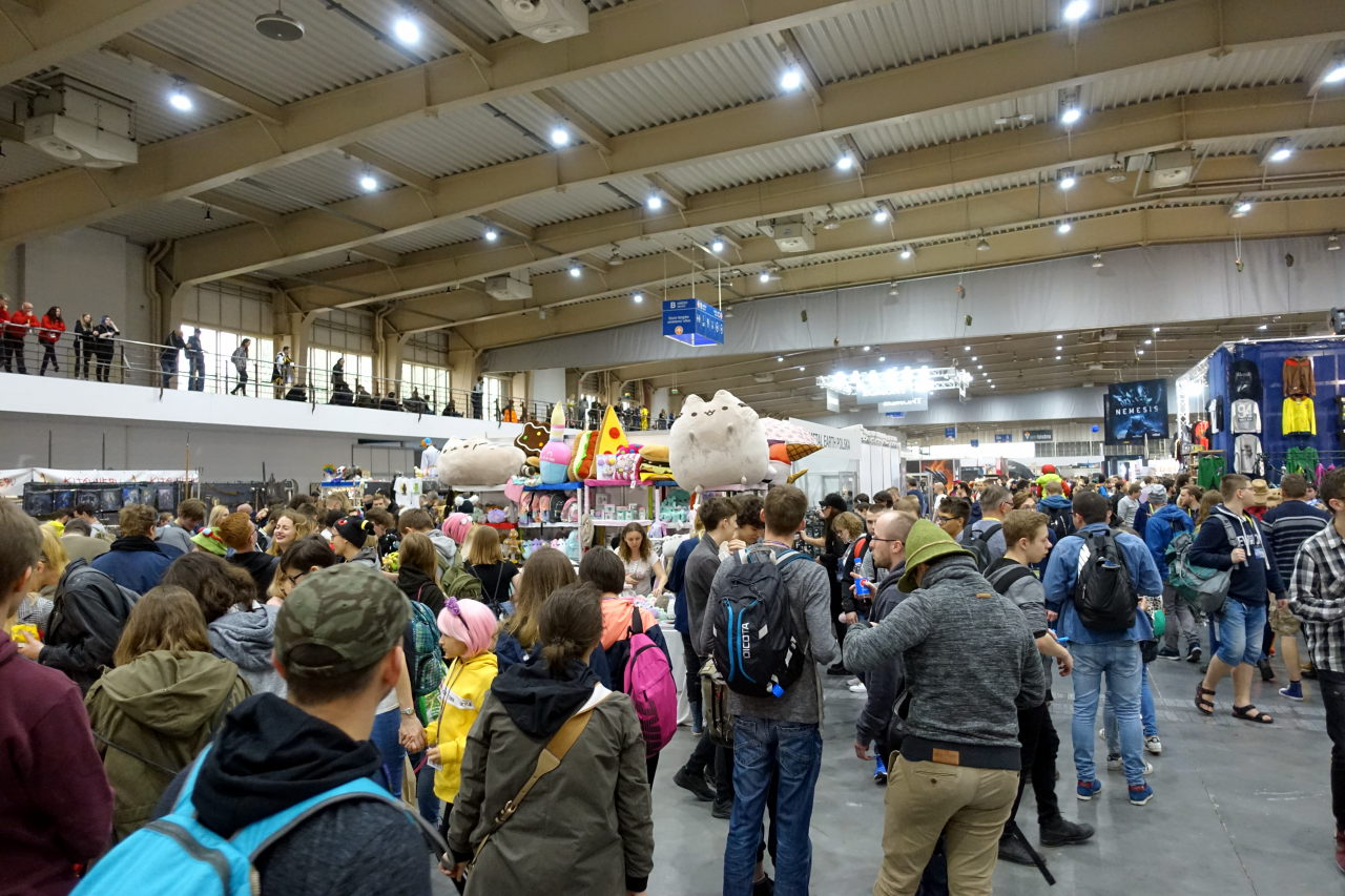 Interior of a large hall with multiple people. One of the stalls is selling giant Pusheen plushies.