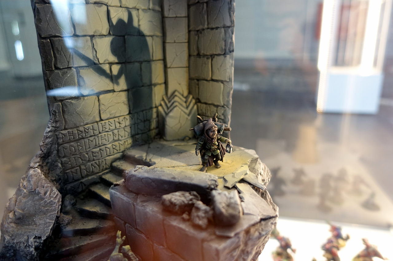 Small diorama showing a halfling in some corridor. The shadow behind him looks like a big warrior with a sword.