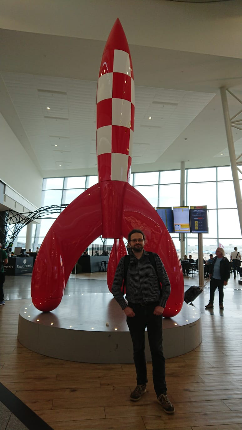 Man standing on fron of the huge rocket from Tintin comic.