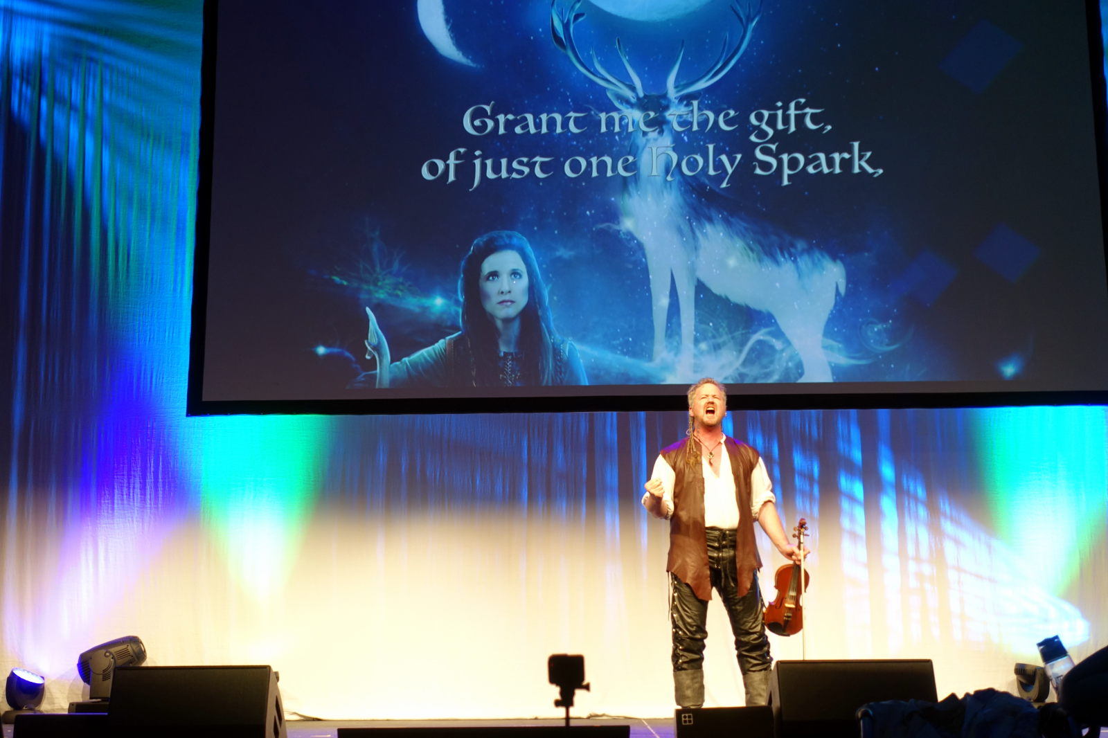 Person standing on a stage with a violin in his hand. Behind the person there is a screen with woman, deer and text: 'Grant me the gift, of just one holy Spark'.