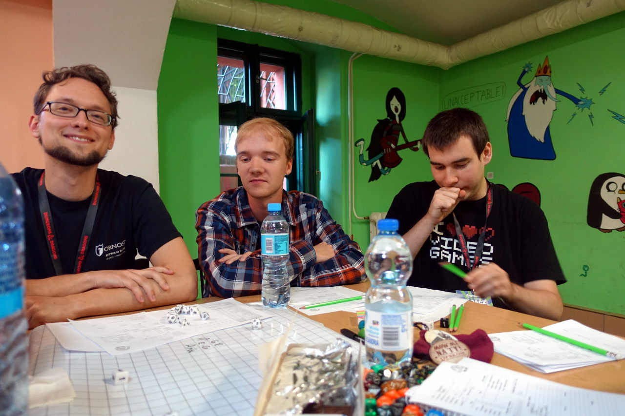 Three people sitting behind a table - one of them is smiling. There are water bottles, dice and a map on the table.
